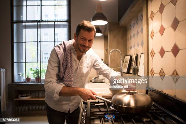 Portrait of smiling man cooking at home