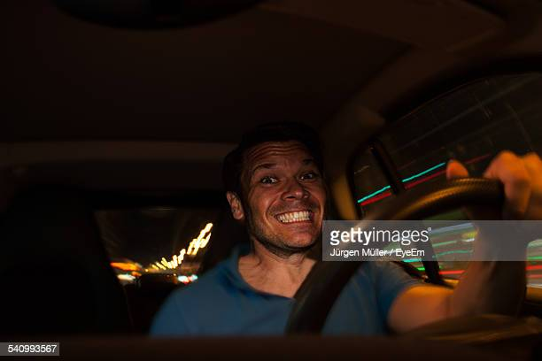 Portrait Of Smiling Man Driving Car At Night