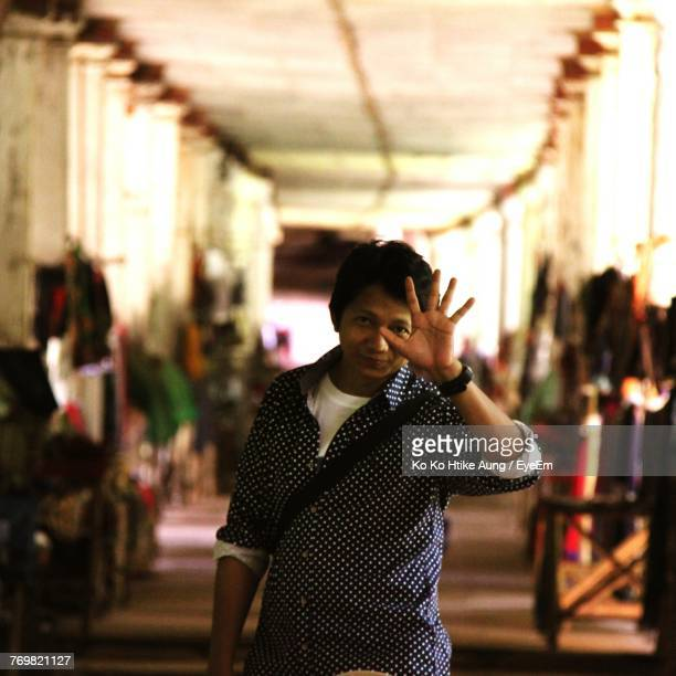 portrait of smiling man gesturing in corridor - ko ko htike aung stock pictures, royalty-free photos & images