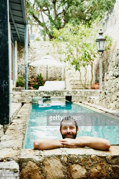 Portrait of smiling man hanging out in pool in courtyard of boutique hotel
