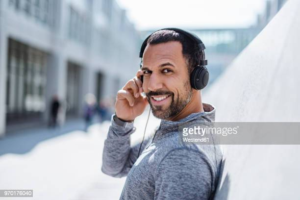 Portrait of smiling man having a break from exercising wearing headphones
