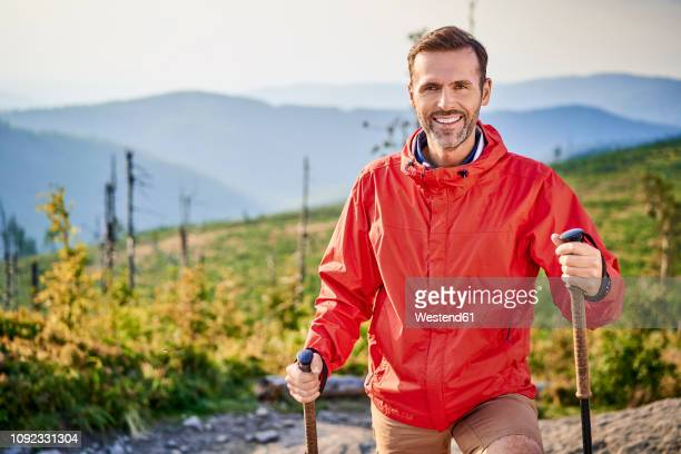 portrait of smiling man hiking in the mountains - jacke stock-fotos und bilder