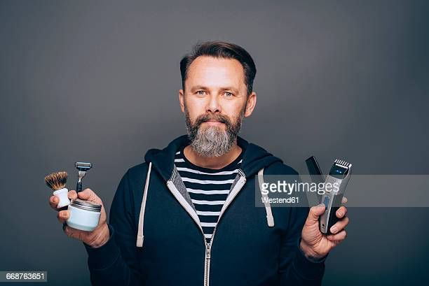 Portrait of smiling man holding accessories for shaving