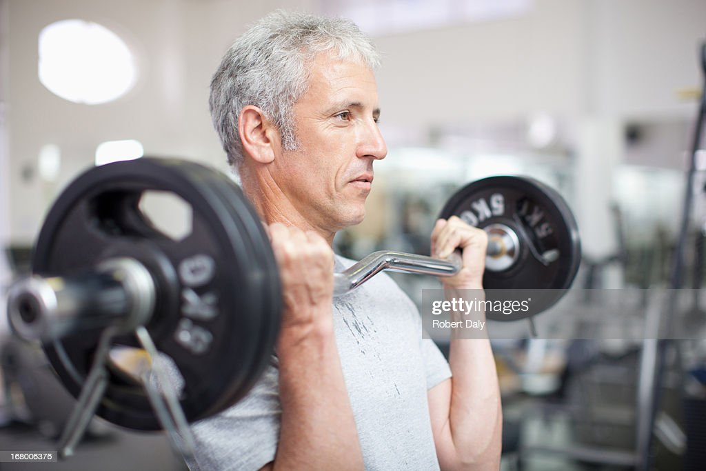 Portrait of smiling man holding barbell in gymnasium : Stock Photo