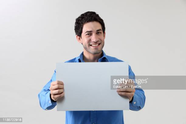 portrait of smiling man holding blank placard against white background - halten stock-fotos und bilder