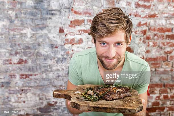 Portrait of smiling man holding board with steak