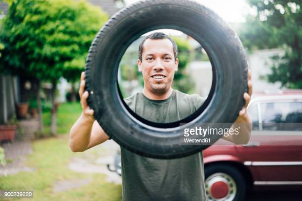 Portrait of smiling man holding car tyre