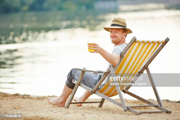 portrait of smiling man holding drink while sitting on deck chair at beach - deck chair stock pictures, royalty-free photos & images