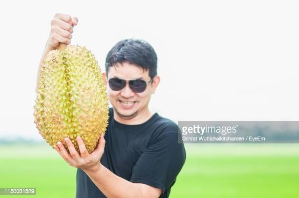 portrait of smiling man holding durian on field - durian stock pictures, royalty-free photos & images