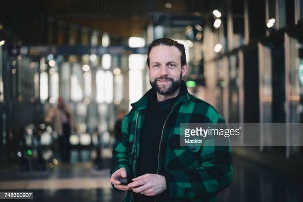 Portrait of smiling man holding mobile phone while standing at railroad station