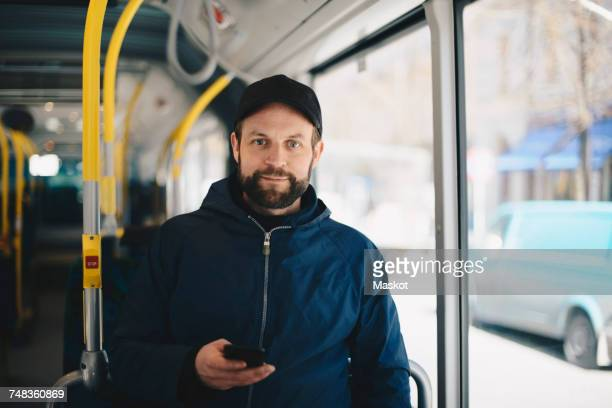 Portrait of smiling man holding mobile phone while standing in bus during sunny day