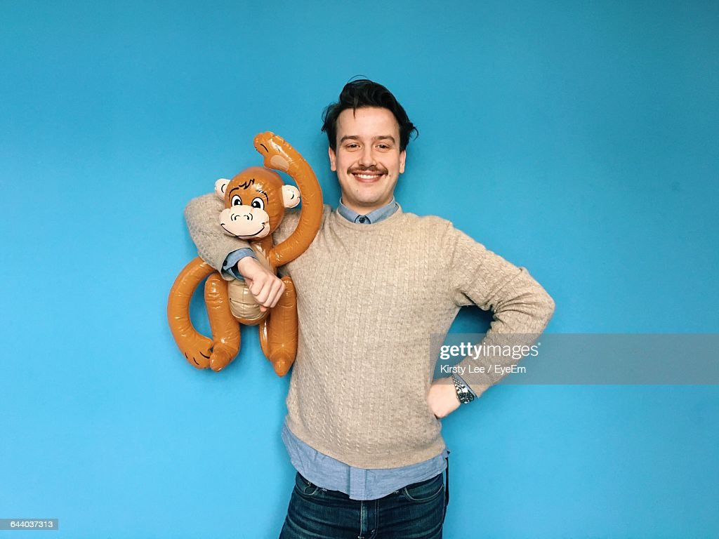 Portrait Of Smiling Man Holding Toy Against Blue Background : Stock Photo