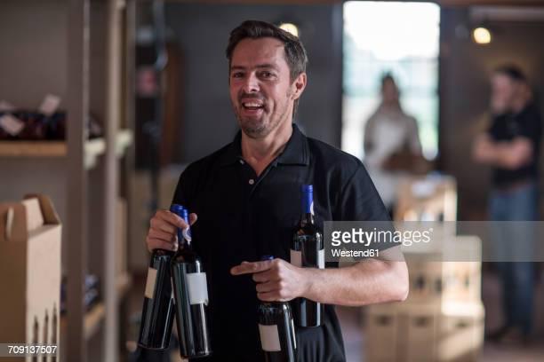 Portrait of smiling man holding wine bottles in shop