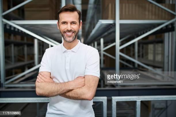 portrait of smiling man in a factory - maglietta polo foto e immagini stock