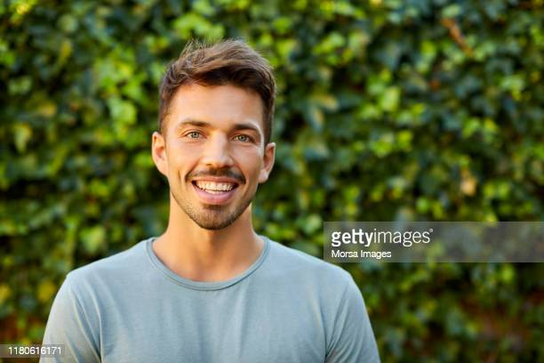 portrait of smiling man in blue t-shirt at backyard - barba por fazer imagens e fotografias de stock