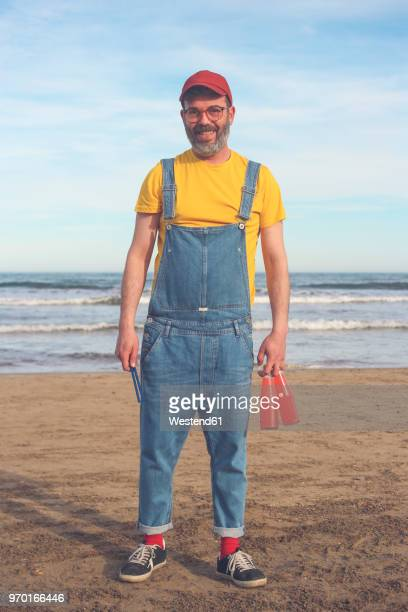 portrait of smiling man in dungarees standing on the beach holding bottles of soft drinks - dungarees stock pictures, royalty-free photos & images