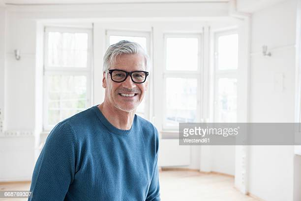 Portrait of smiling man in empty apartment