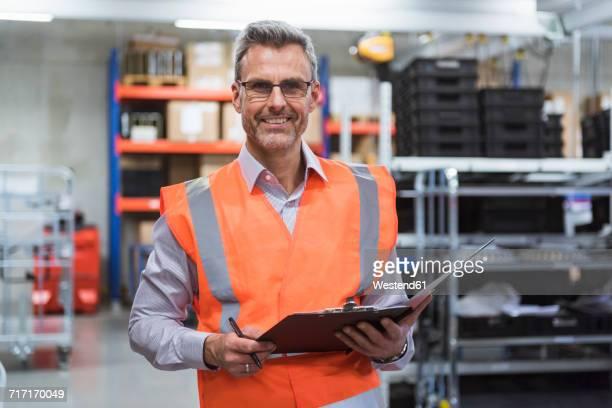 portrait of smiling man in factory hall wearing safety vest holding clipboard - klemmbrett stock-fotos und bilder