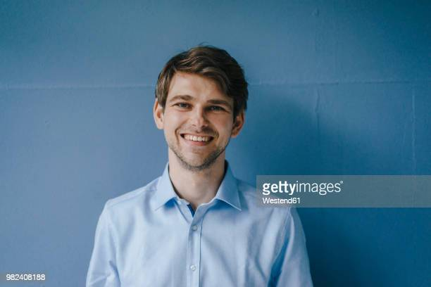 portrait of smiling man in front of blue wall - einzelner mann über 30 stock-fotos und bilder