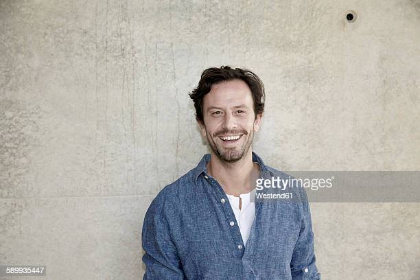 portrait of smiling man in front of concrete wall - männer über 30 stock-fotos und bilder