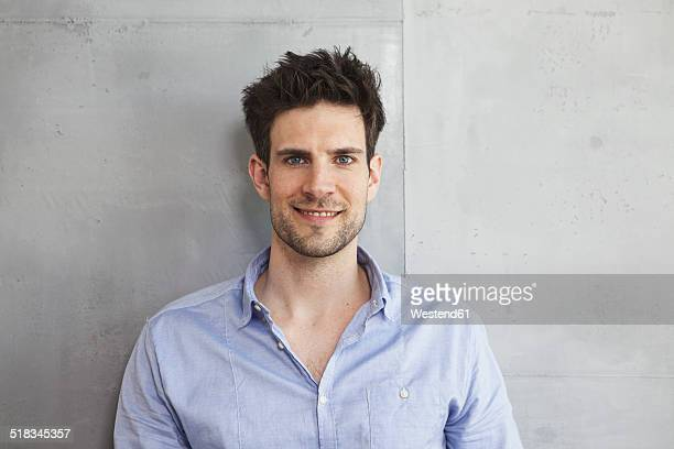 Portrait of smiling man in front of grey wall