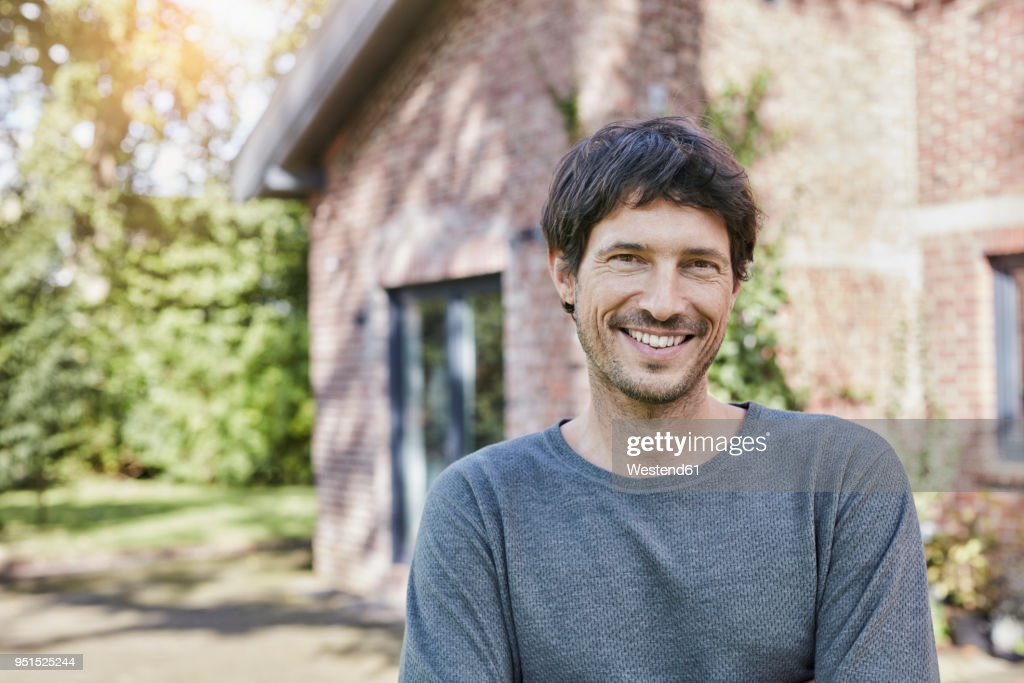 Portrait of smiling man in front of his home : Stock-Foto