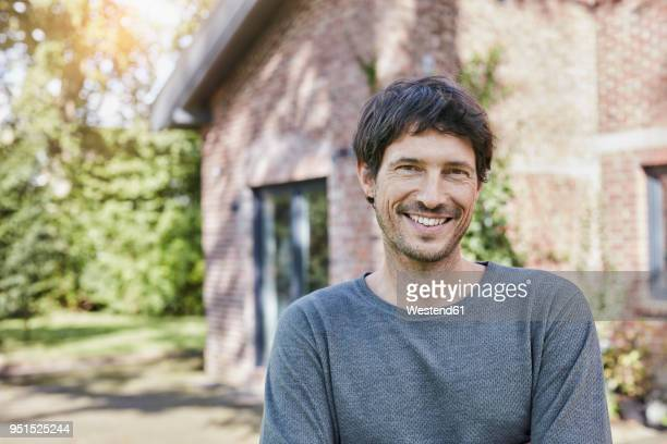 portrait of smiling man in front of his home - ein mann allein stock-fotos und bilder