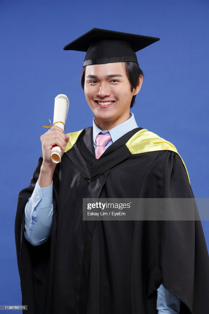 Portrait Of Smiling Man In Graduation Gown Holding Certificate Over Blue Background : Stock Photo
