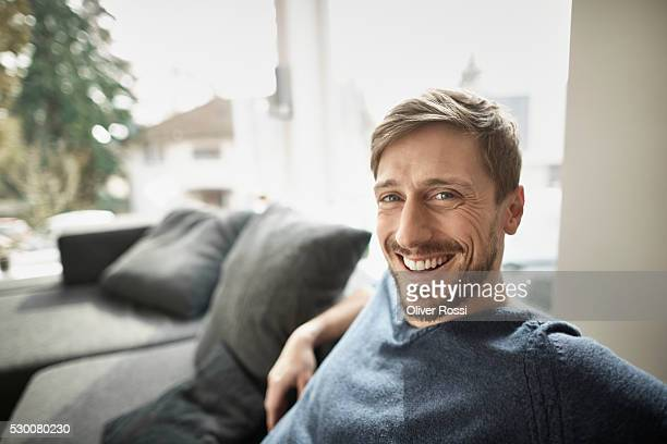 portrait of smiling man in living room - 35 39 years stock pictures, royalty-free photos & images