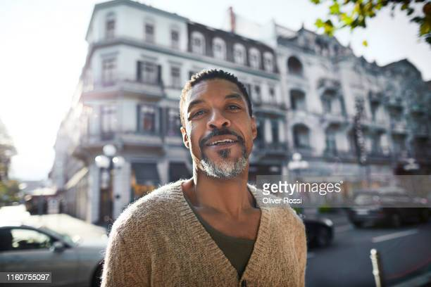 portrait of smiling man in the city - regardant l'objectif photos et images de collection