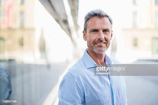 portrait of smiling man in the city - homem 45 anos imagens e fotografias de stock