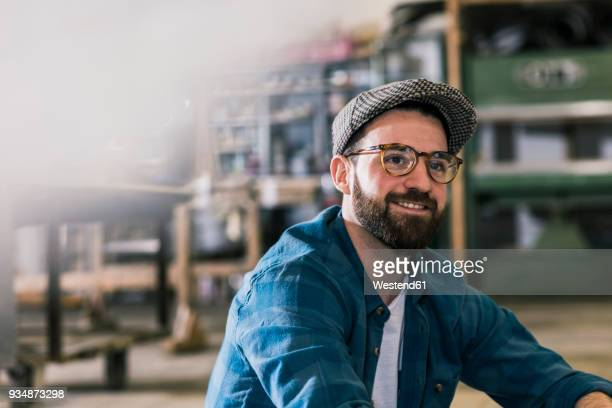 portrait of smiling man in workshop - 25 29 jaar stockfoto's en -beelden