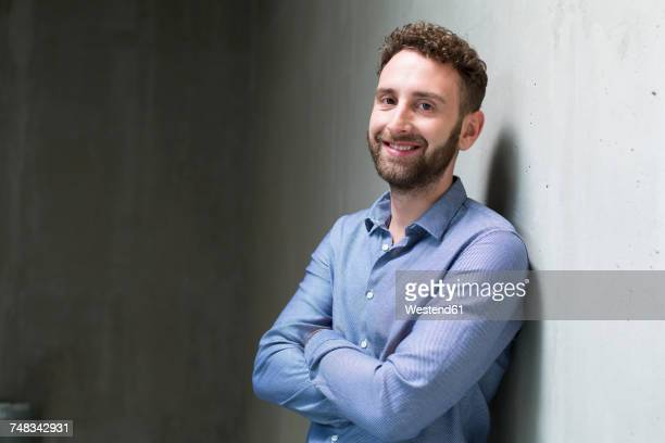Portrait of smiling man leaning against concrete wall