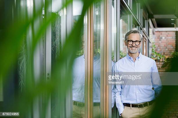 portrait of smiling man leaning against facade of his house - shirt stock pictures, royalty-free photos & images
