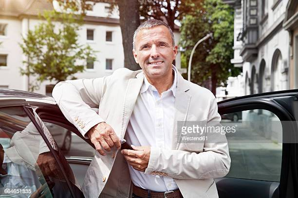 Portrait of smiling man leaning at open car door with car keys
