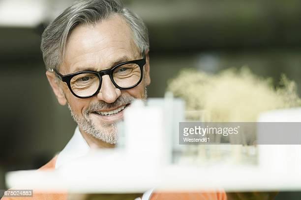 portrait of smiling man looking at architectural model - architekturberuf stock-fotos und bilder
