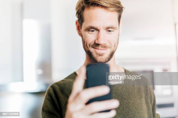 portrait of smiling man looking at cell phone - männer über 30 stock-fotos und bilder