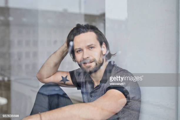 Portrait of smiling man looking out of window