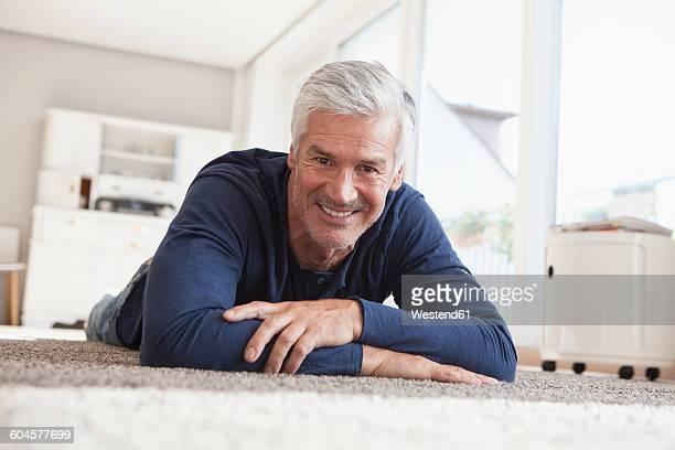 portrait of smiling man lying on the floor at home - acostado boca abajo fotografías e imágenes de stock