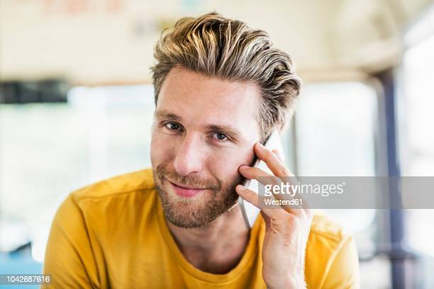 portrait of smiling man on cell phone - in den dreißigern stock-fotos und bilder