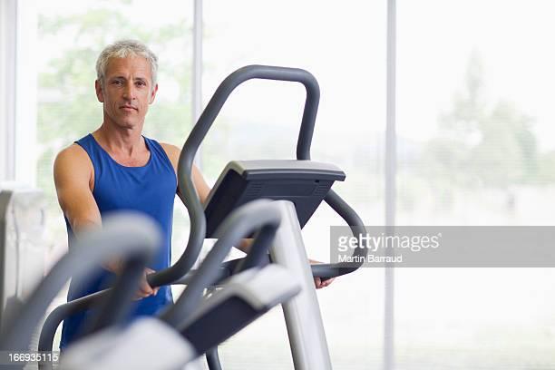 Portrait of smiling man on elliptical machine in gymnasium
