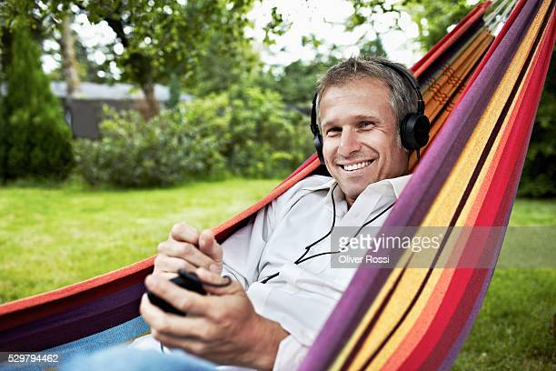 Portrait of smiling man on hammock wearing headphones