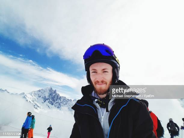 portrait of smiling man on snow mountain against sky - ski wear stock pictures, royalty-free photos & images