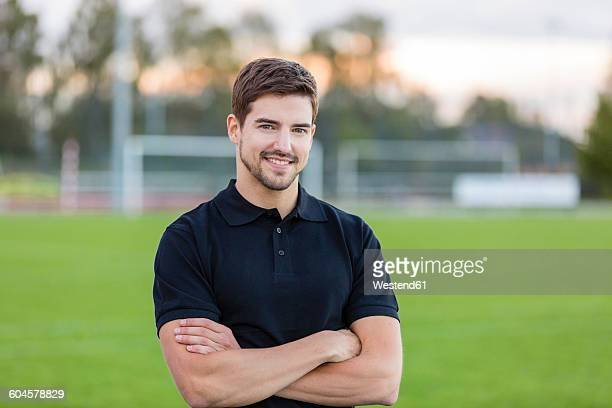 portrait of smiling man on sports field - polo shirt stock pictures, royalty-free photos & images