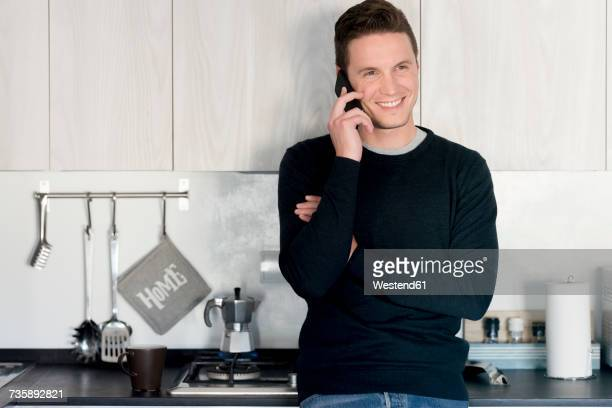 Portrait of smiling man on the phone in the kitchen