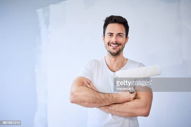 portrait of smiling man painting wall in apartment - maler stock-fotos und bilder