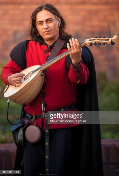 portrait of smiling man playing musical equipment while standing outdoors - steve guessoum stockfoto's en -beelden
