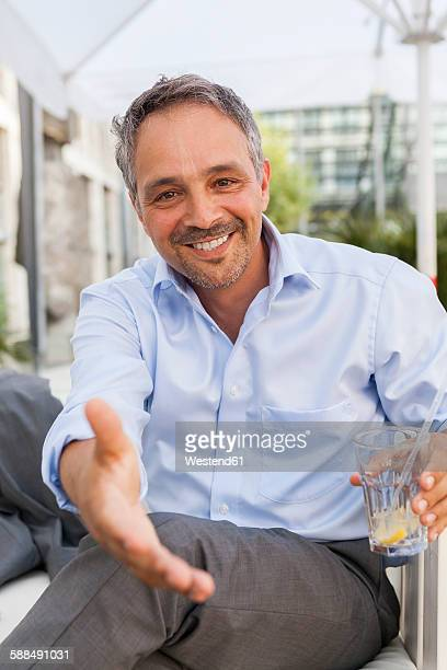 Portrait of smiling man reaching out his hand
