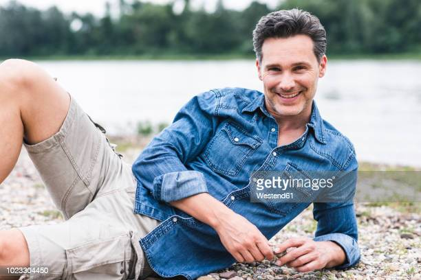 portrait of smiling man relaxing at the riverside - lying on side stock pictures, royalty-free photos & images