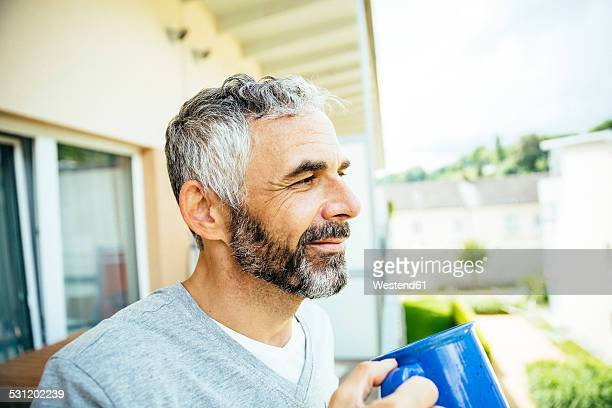 Portrait of smiling man relaxing with cup of coffee on his balcony